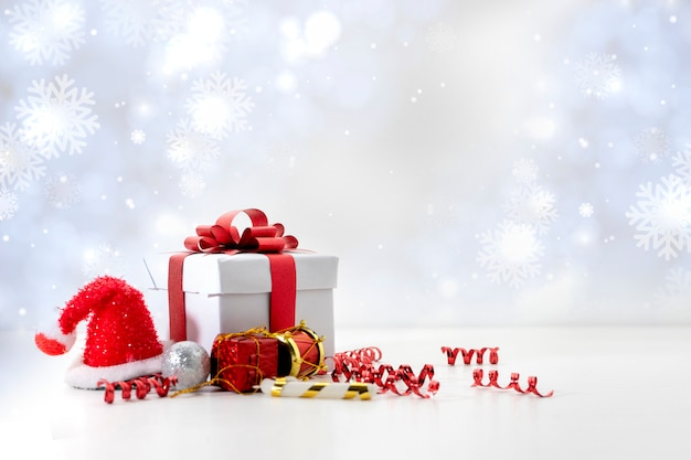 Objets de fête boîte cadeau rouge sur fond blanc, lumières de noël bokeh