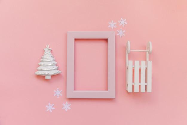 Objets d'hiver de composition tout simplement minimale cadre rose ornement sapin luge isolé sur pastel rose