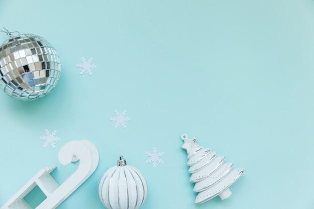 Objets d'hiver de composition tout simplement minimaliste boule de sapin de traîneau ornement isolé sur bleu pastel