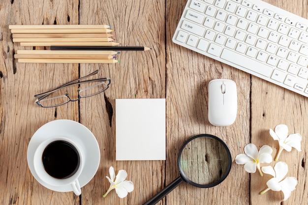 Objets métier de clavier, souris, tasse à café blanche, papier blanc, crayons, lunettes, loupe