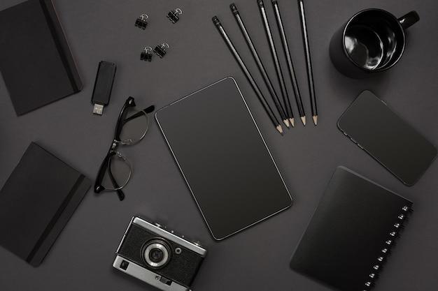 Objets noirs du bureau sur fond gris foncé, vue de dessus du travail et de la créativité