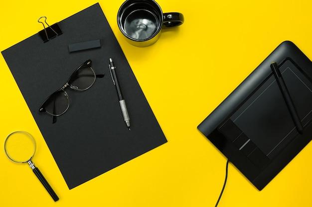 Objets noirs du bureau sur fond jaune. travail et créativité. image d'en-tête de héros de concept de médias sociaux. vue de dessus. nature morte. espace de copie