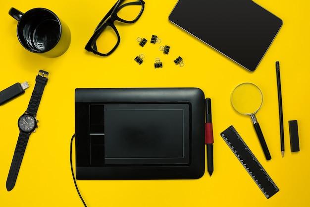 Objets noirs du bureau sur fond jaune vue de dessus de travail et de créativité