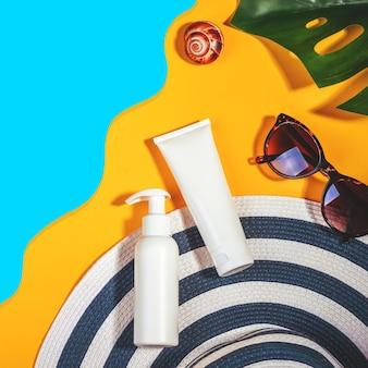 Objets de protection solaire. bonnet femme avec crème de protection lunettes de soleil, pose plate