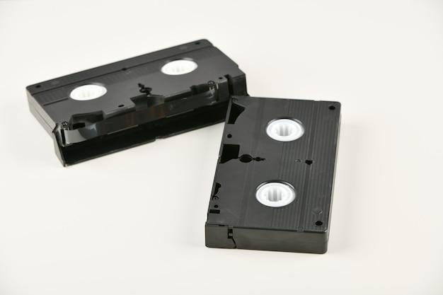 Objets rétro sur fond blanc. téléphone à bouton-poussoir et cassette vidéo. la technologie des médias analogiques du passé. espace copie