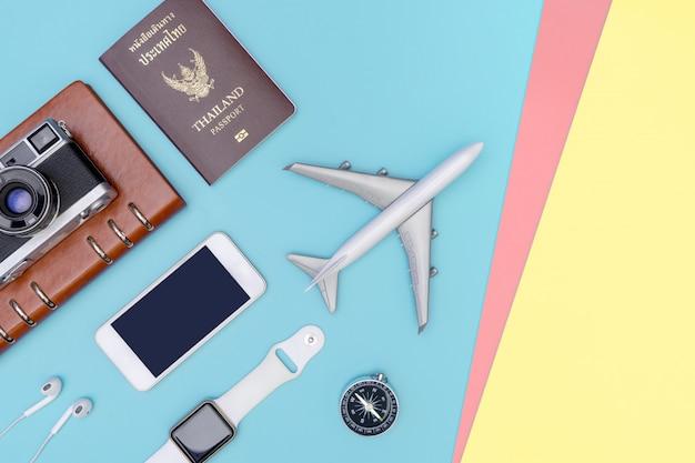 Objets de voyage et accessoires sur fond rose jaune bleu avec caméra passeport et avion