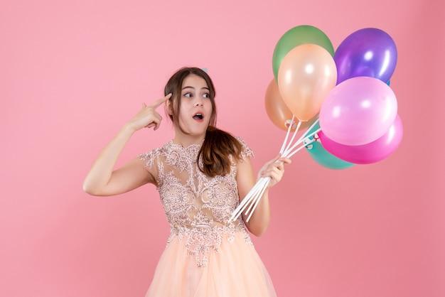 Observant une fille de fête avec chapeau de fête tenant des ballons sur rose