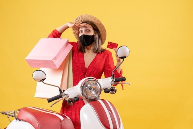 Observant une jeune femme avec un masque noir tenant une carte de crédit et des sacs à provisions près d'un cyclomoteur