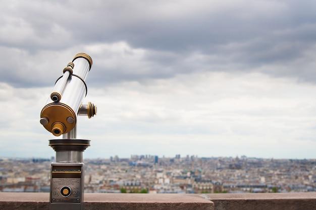 Observateur de télescope et les toits de la ville pendant la journée.