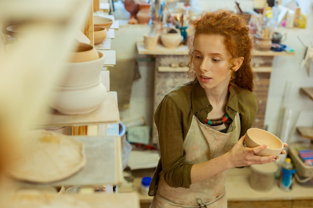 Observation du pot fini. femme bouclée positive traitant des pots en argile en studio tout en restant près des étagères