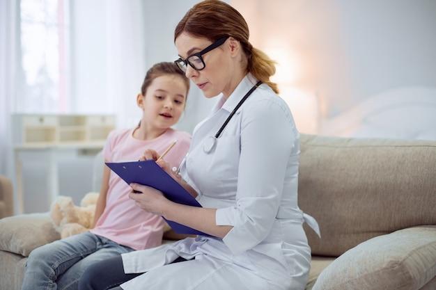 Observation importante. femme médecin sérieusement concentrée assise sur un canapé tout en portant des lunettes et en notant les symptômes