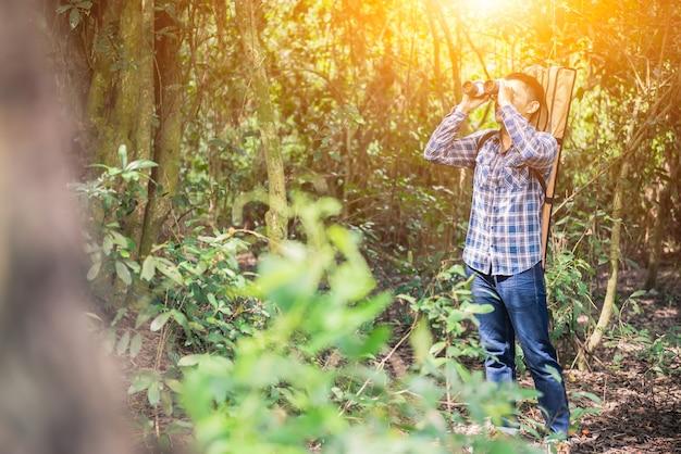 Observation de l'ird et sentier de randonnée en forêt. activités de plein air et loisirs pendant les vacances d'été. touriste tenant des jumelles