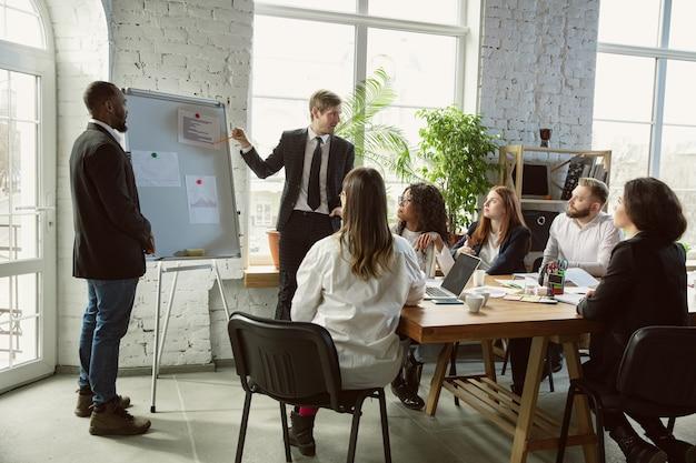 Obtenez la cible. groupe de jeunes professionnels ayant une réunion. un groupe diversifié de collègues discute de nouvelles décisions, plans, résultats, stratégie. créativité, lieu de travail, affaires, finance, travail d'équipe.