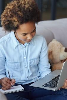 Obtenez une nouvelle écolière adolescente axée sur les connaissances en utilisant un ordinateur portable en prenant des notes pendant la leçon en ligne tout en