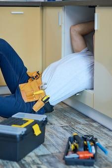 Obtenez un plombier professionnel portant une ceinture à outils examinant et réparant le tuyau d'évier à l'intérieur des outils et