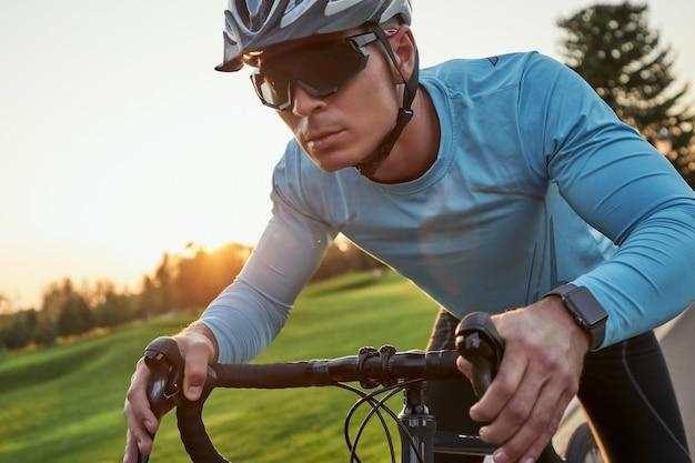 Obtenez plus rapidement un jeune coureur masculin sérieux dans des vêtements de sport et un casque de protection qui a l'air concentré pendant la conduite
