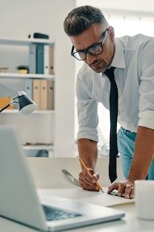 Obtenir les meilleurs résultats. beau jeune homme dessinant quelque chose tout en travaillant au bureau
