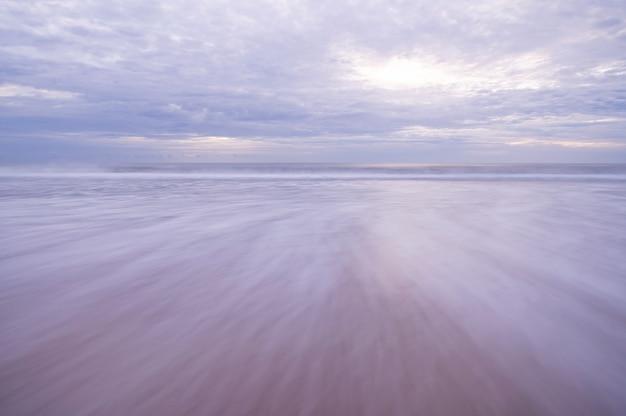 Obturateur longue vitesse de plage de sable tropicale avec ciel et nuages au-dessus de la mer.