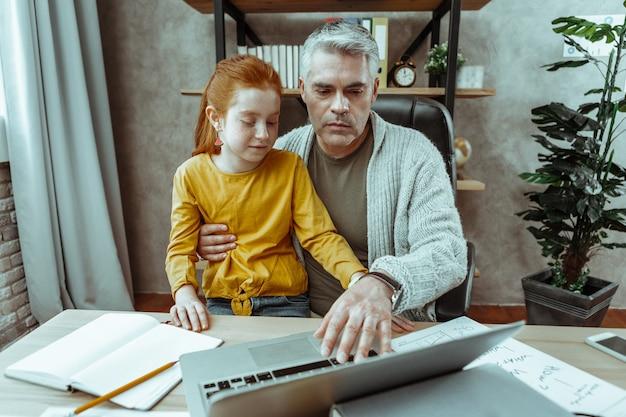 Occupé avec du travail. bel homme sérieux tenant sa fille tout en appuyant sur le bouton de son ordinateur portable