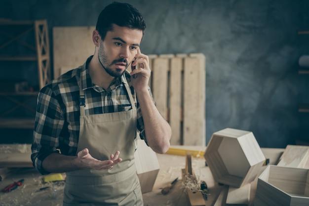 Occupé inquiet, contremaître surchargé, bricoleur, parler sur smartphone, avoir des problèmes avec les clients, décider offre des commandes de réparation de restauration de construction de meubles sur le lieu de travail à domicile