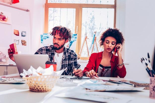 Occupé et surchargé. des artistes talentueux créatifs occupés se sentant occupés et surchargés lorsqu'ils reçoivent des appels