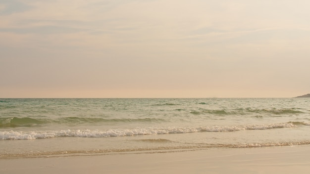 Ocean beach waves sur une plage tropicale au coucher du soleil
