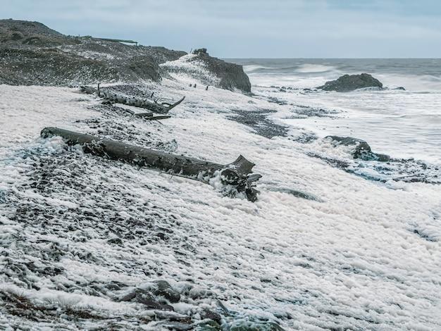 Océan orageux. des vagues avec de la mousse blanche roulent sur le rivage rocheux. côte tersky, cape ship jusqu'à la péninsule de kola.