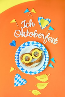 Octoberfest creative flat lay on paper orange with text, bretzels and blue-white decorations