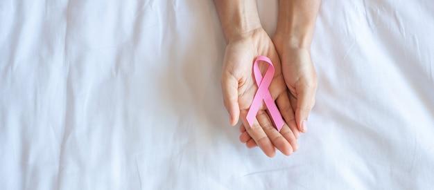 Octobre mois de sensibilisation au cancer du sein, main de femme adulte tenant un ruban rose sur fond rose pour soutenir les personnes vivant et malades. concept de la journée internationale des femmes, des mères et du monde contre le cancer