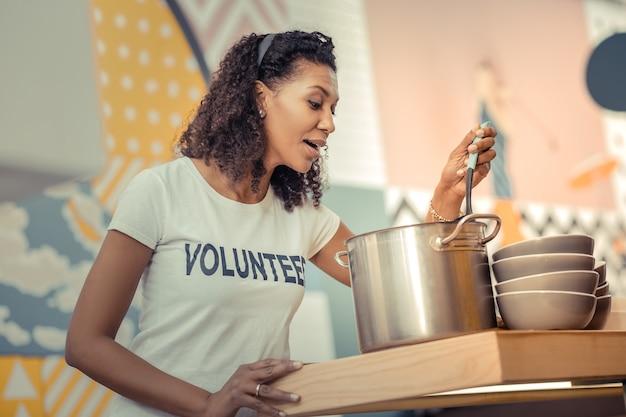 Odeur agréable. joyeuse belle femme préparant du bouillon de poulet tout en travaillant comme bénévole