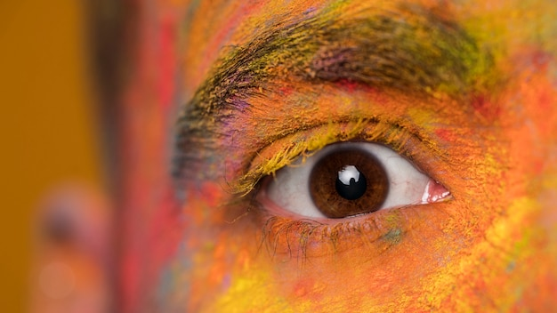 Oeil brun de jeune homme avec le maquillage artistique brillant holi