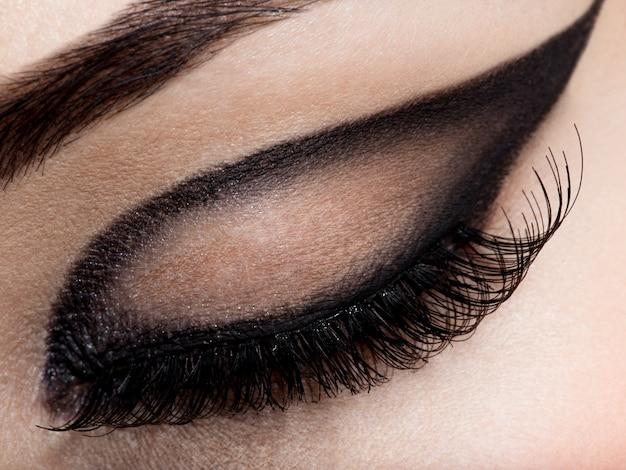 Oeil féminin gros plan avec maquillage mode créatif. fard à paupières marron
