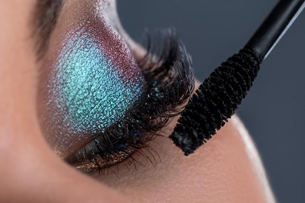 Œil féminin avec une longue brosse en lashesh et mascara