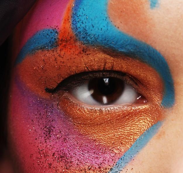 Œil féminin avec un maquillage créatif vif