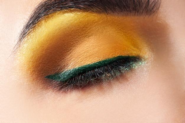 Oeil de femme fermé avec maquillage jaune et bande verte en studio