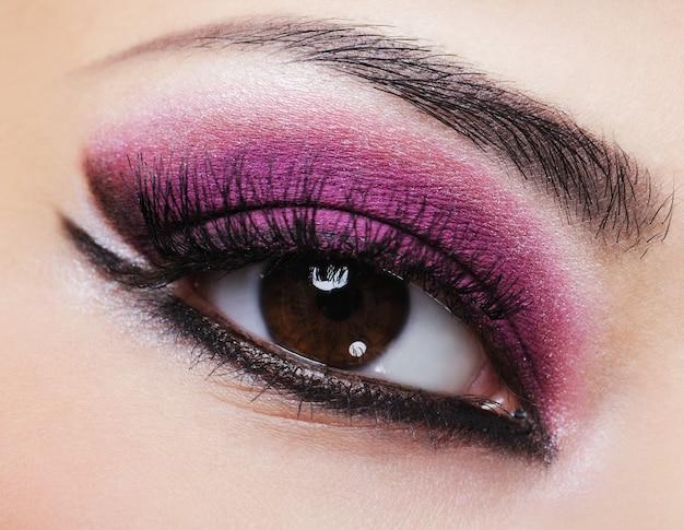Oeil de femme avec maquillage lumineux violet