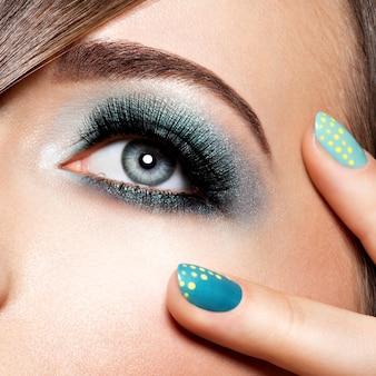 Oeil de femme avec un maquillage turquoise. faux cils longs. coup de macro