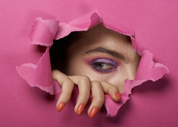 Oeil de fille avec du maquillage dans un trou de papier déchiré rose.