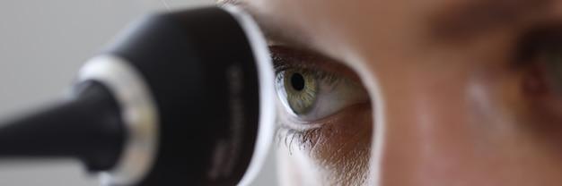Oeil de l'oto-rhino-laryngologiste à la recherche à travers l'otoscope en clinique