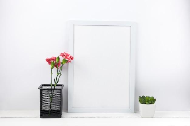 Oeillet fleurs pot et plante succulente avec cadre vide à la maison