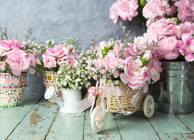 Oeillet rose en panier vélo sur vieux bois