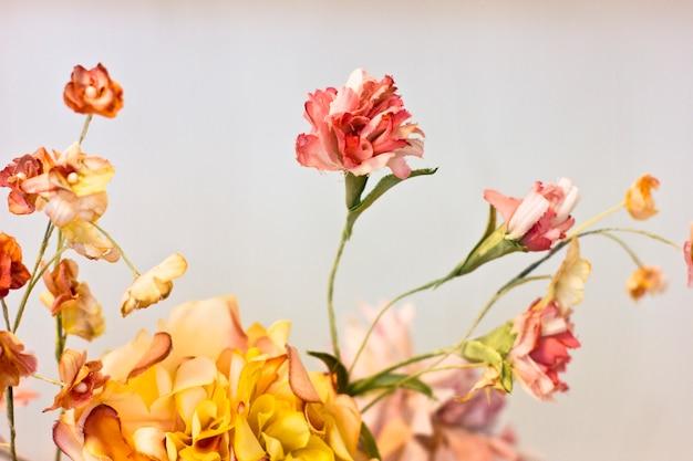 Oeillets roses et chrysanthèmes orange dans un vase blanc.