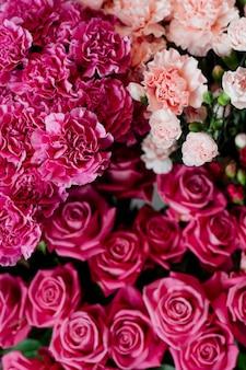 Oeillets roses et pêche avec des roses roses dans un magasin de fleurs