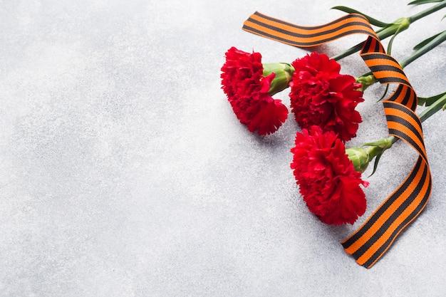 Oeillets rouges et ruban st. george sur un fond de béton.