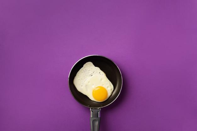 Oeuf au plat sur une casserole sur fond violet