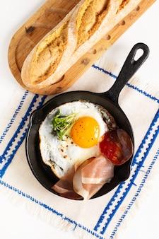 Oeuf au plat dans une poêle en fer poêle avec des pousses de lin et du bacon avec espace de copie