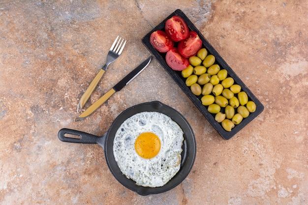 Oeuf au plat dans une poêle servi avec des olives vertes marinées