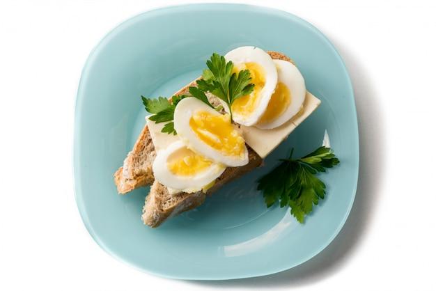 Oeuf au plat avec du pain et du persil sur la plaque bleue
