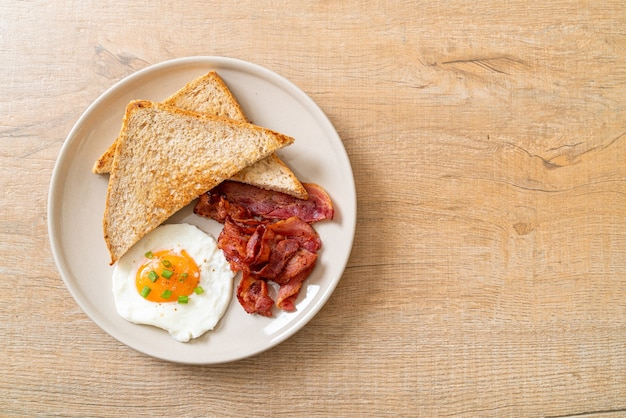 Oeuf au plat avec du pain grillé et du bacon pour le petit déjeuner