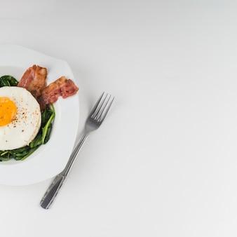 Oeuf au plat avec épinards et bacon sur plaque sur fond blanc